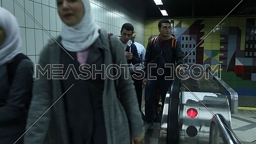 Fixed shot inside Metro Station for people going up with electric ladder at Cairo