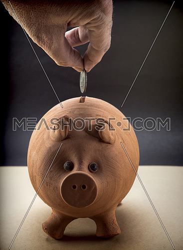 Hand throwing a currency in a moneybox of piglet of mud, conceptual image