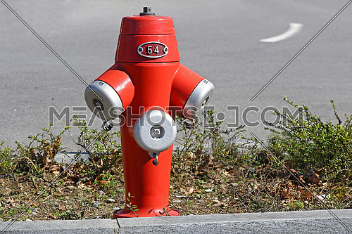Red fire hydrant in the sun between two lanes of a city road