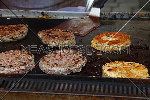 Close up beef meat burgers and vegetarian quinoa burgers for fast food hamburgers cooked on barbecue grill, high angle view