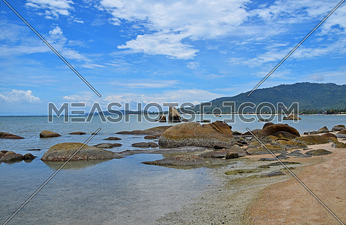 Beautiful sunny and cloudy day seascape with rock formations in sea water near shore