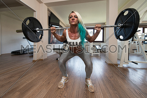 Middle Aged Woman Performing Barbell Squats - One Of The Best Bodybuilding Exercise For Legs