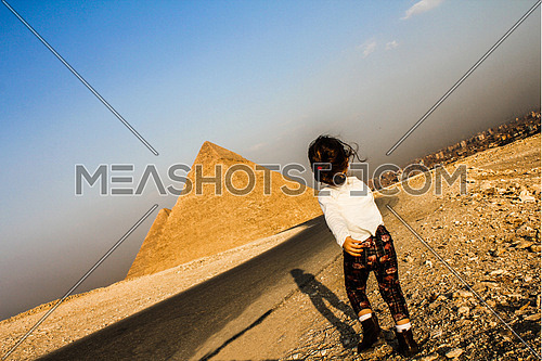 A little girl running to the Pyramids