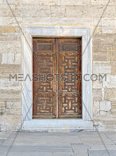 Wooden aged vaulted engraved door and exterior stone wall, Sultan Ahmet Mosque, Istanbul, Turkey
