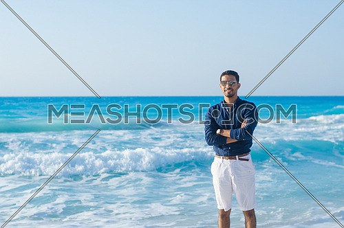 A man wearing shorts and shirt posing by the sea