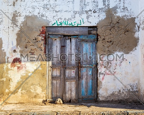 Closed wooden weathered door and shabby old grunge stone wall on abandoned district. Arabic text above door translates to: For Rent