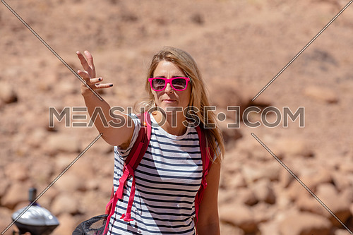 Mid shot for a female tourist wearing a pink glasses and travel backpack taking exploring at Sinai Mountain for wadi Freij by day.
