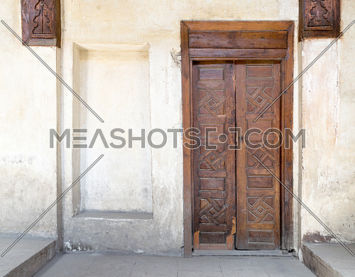 Wooden aged closed decorated door and beige plaster wall, Medieval Cairo, Egypt