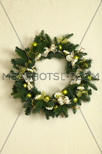 Close up green Christmas wreath decoration on beige wall, front view