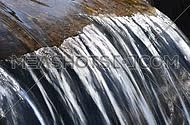 Brook water stream with small rift in day time, close up