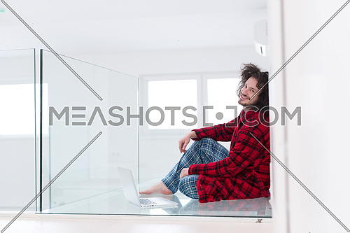 young freelancer in bathrobe working from home using laptop computer while sitting on floor