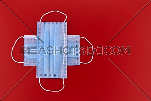 Crossed protective surgical face masks over a red background with copyspace