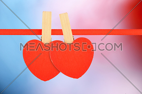 Valentine day love template, two red wooden hearts with clothes pins on textile ribbon on multicolor background