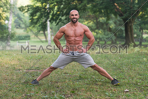 Young Muscular Athlete Doing Stretching As Part Of Bodybuilding Training - Outdoors Workout - Sports And Fitness - Concept Of Healthy Lifestyle - Fitness Male