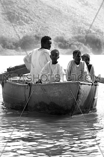3 children and an adult in a rowing boat in the river NILE