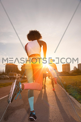 young black girl on the jogging beautiful morning as the sun rises in the streets of the city