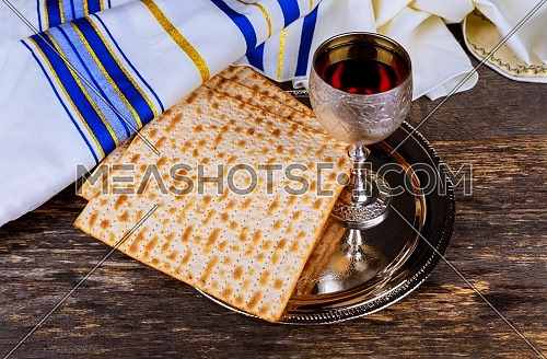 Table ready for traditional seder plate ritual the Jewish holiday of Passover kiddush wine cup, haggada, matzos, lettuce