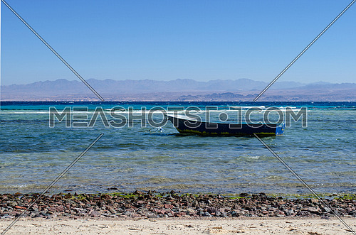 a small blue boat at the beach with no body in it