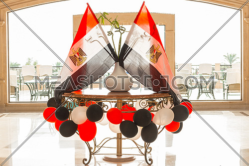 Egyptian flags in backlight, around colored balloons, in a hotel lobby