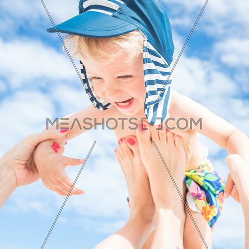 Mom throws up her smiling baby boy in the blue sky,summer time.
