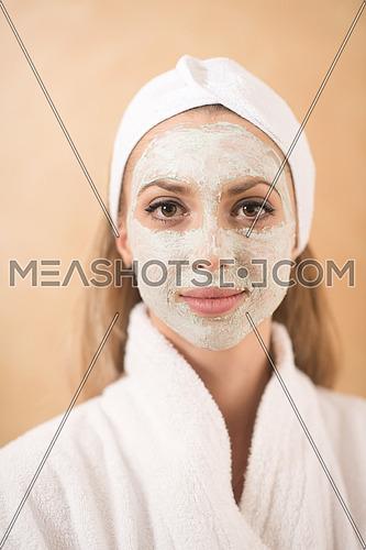 portrait of beautiful woman with cosmetic mask on face in spa and  wellness salon
