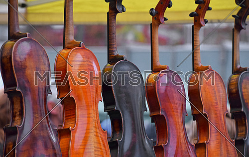 Close up many old vintage antique violins for sale at retail market display, low angle view