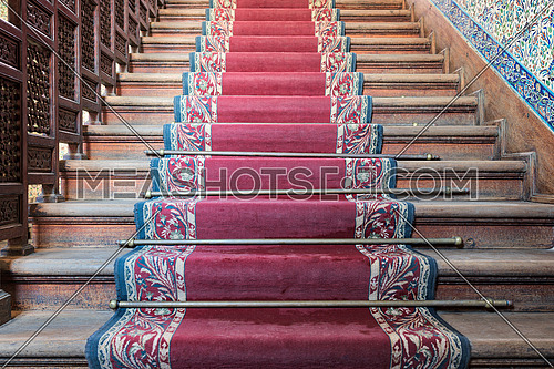 Front view of old ascending wooden stairs with ornate red carpet and wooden balustrade, Manial Palace of Mohamed Ali, Cairo, Egypt