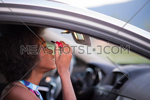 young beautiful African American woman enjoys while makeup herself in the car