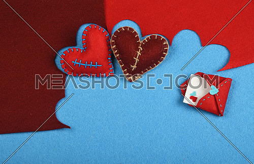 Felt craft and art, two handmade stitched toy hearts, brown and red cut out on blue felt background, with letter envelope