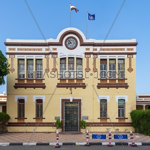 Facade of Financial Affairs Department of Suez Canal Authority with yellow bricks, Single door, windows covered with iron bars, and clock at the top of the building, located in Port Fuad, Cairo, Egypt