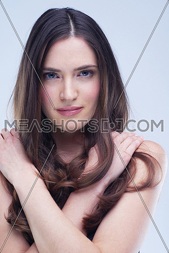 portrait of young nude brunette woman isolated in studio