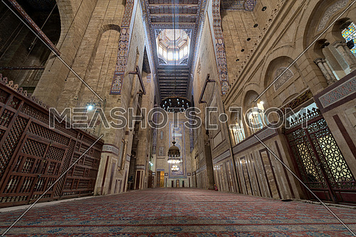 Interior of al Refai mosque with old decorated bricks stone wall, colored marble decorations, wooden ornate ceiling, big brass chandeliers, and wooden latticework door, Cairo, Egypt