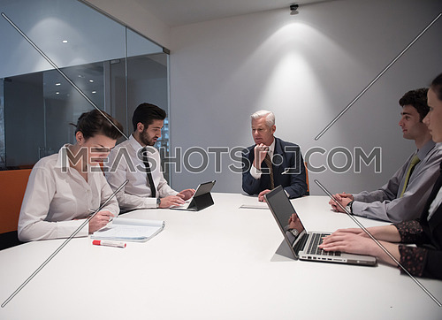 business people group brainstorming on meeting and businessman presenting ideas and projects oon laptop and tablet computer