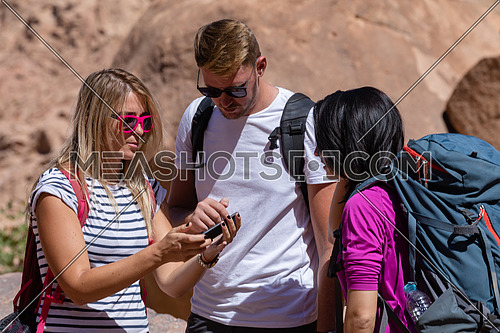mid shot for a group of tourists wearing backpacks standing and talking while exploring Sinai Mountain for wadi Freij at day.