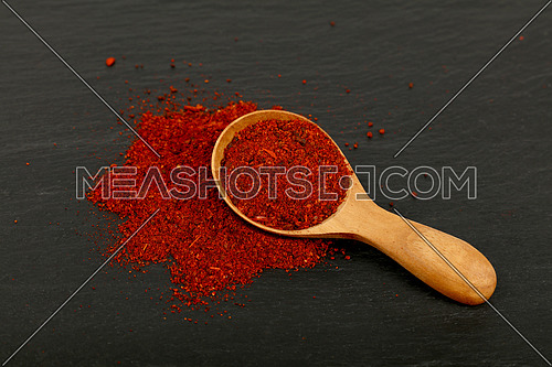 Close up one wooden scoop spoon full of ground sun dried tomato or red chili pepper on background of black slate cooking board, high angle view