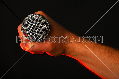Male hand holding microphone highlighted with red gun projector isolated on black background