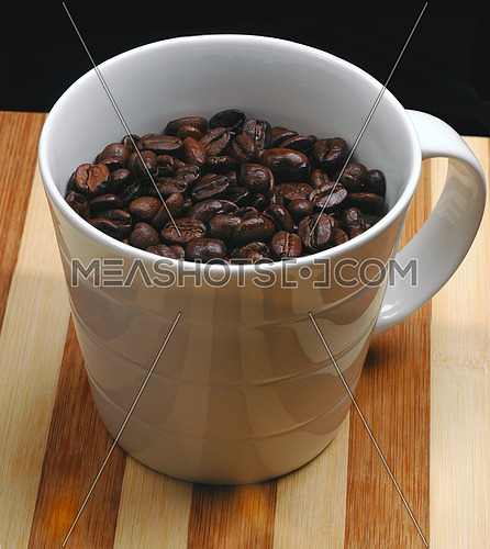 coffee beans on a cup  on a wood board