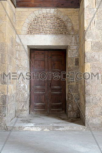 Wooden aged vaulted ornate door and stone wall at Qalawun Complex, Medieval Cairo, Egypt