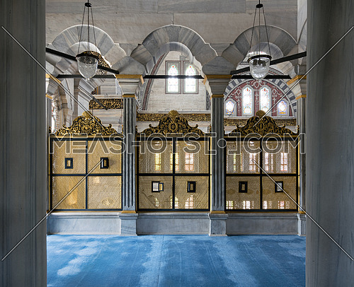 Three gold painted decorated Interleaved wooden windows (Mashrabiya) framed by three marble arches, marble wall and blue carpet on the second floor terrace of Nuruosmaniye Mosque, Istanbul, Turkey