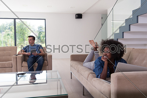 Young multiethnic couple relaxes in the luxury living room, using a tablet and laptop computer
