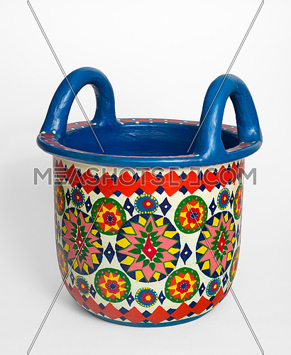 Handmade artistic pained colorful decorated pottery basket with two handles on white background