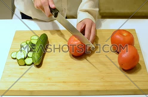 female hands cutting tomatos