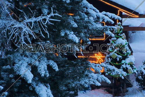 christmas tree outdoor decoration in a snowy night with gifts and illuminatedn wooden  home