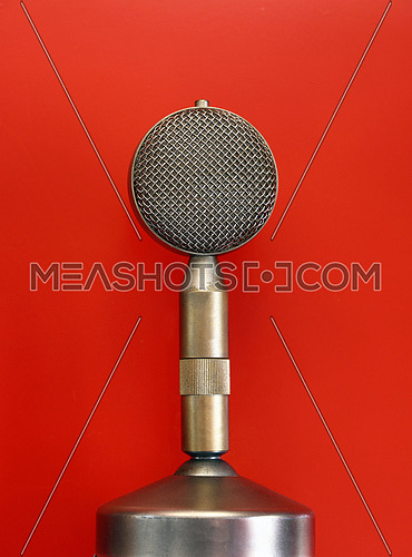 Vintage old retro round vocal metal microphone side view close up over red background