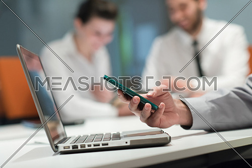 close up of  businessman hands  using smart phone and laptop computer, people group in office meeting  room blurred in backgronud