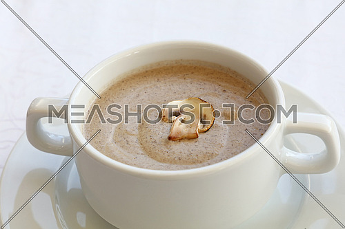 Portion of champignon mushroom cream soup in white porcelain tureen pot on the table, close up, high key, high angle view