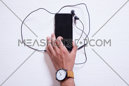 A mobile phone with headphones on a white table