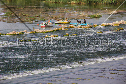 a photo for the river Nile showing the flow of water, boats of fishermen in north of Cairo, Egypt.