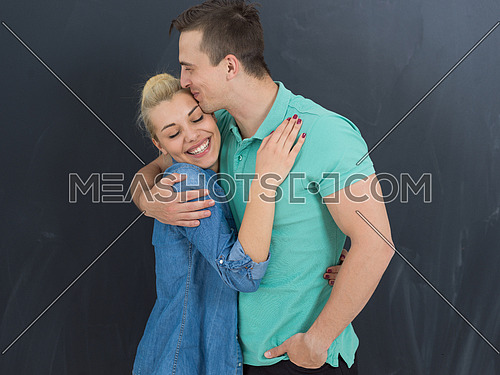 portrait of happy young loving couple in front of gray chalkboard