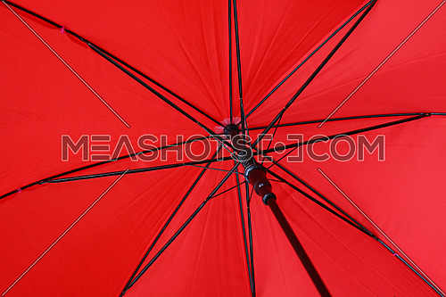 Close up red colorful vivid umbrella personal perspective low angle view